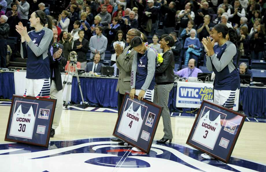 UConn's Moriah Jefferson, center, reacts as teammates Breanna Stewart, left, and Morgan Tuck, right, watch as her number is unveiled on the UConn Huskies of Honor wall at Gampel Pavilion. Photo: Jessica Hill — The Associated Press  / FR125654 AP