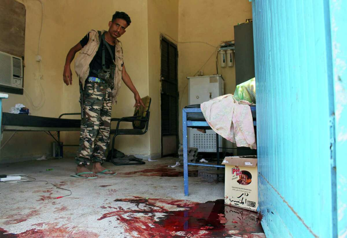 A Yemeni man inspects an elderly care home after it was attacked by gunmen in the port city of Aden, Yemen, Friday, March 4, 2016. Unidentified gunmen stormed a retirement home run by Catholic nuns in the southern city of Aden on Friday shooting more than a dozen people to death, including several Indian nuns, Yemeni security officials and witnesses said.