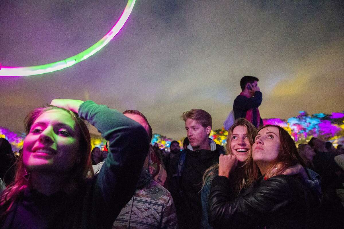 Natalie Sherer (right) embraces Chelsea Emerson as Ashley Zoellner (left) watch the performance by the Gorillaz during the Outside Lands music festival at Golden Gate Park on Friday, Aug. 11, 2017, in San Francisco, Calif.