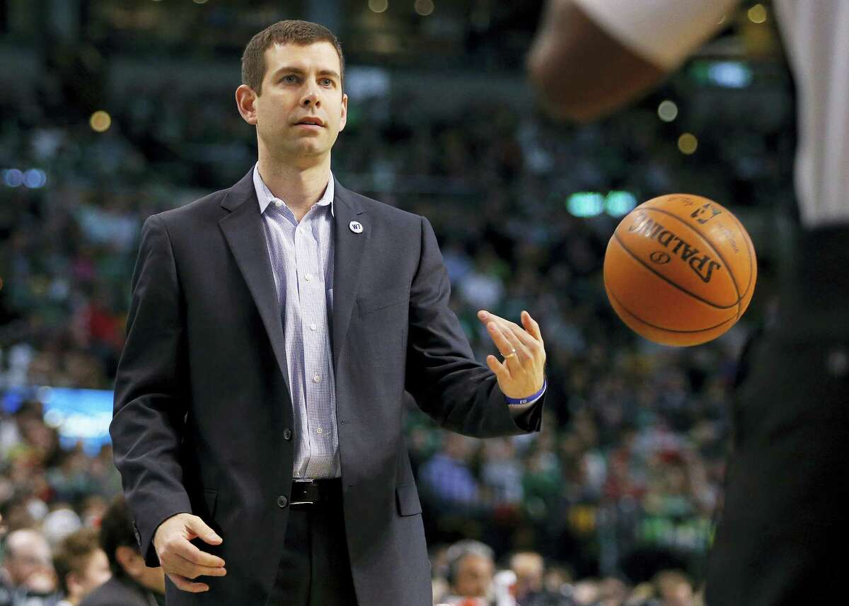 Celtics head coach Brad Stevens flips the ball back to the referee during Saturday's game.