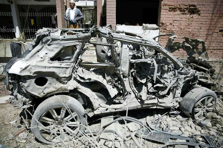 A Yemeni man stands next to a damaged vehicle after an airstrike by Saudi-led coalition in Sanaa, Yemen, Saturday, Feb. 27, 2016. Photo: AP Photo/Hani Mohammed  / AP