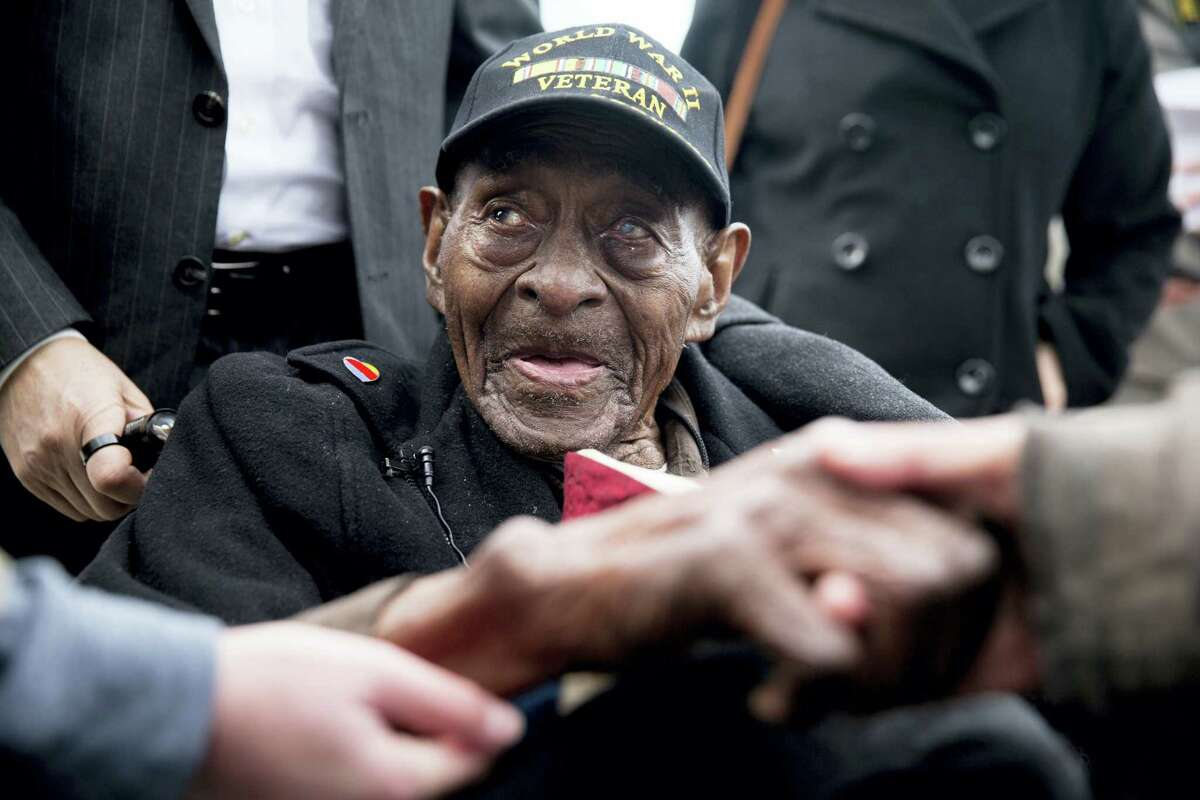 In this Dec. 7, 2015 file photo, Frank Levingston Jr., of Lake Charles, La., is greeted by visitors following a wreath laying ceremony to mark the anniversary of Pearl Harbor at the World War II Memorial in Washington. Levingston, a 110-year-old veteran who served in World War II, died Tuesday, May 3, 2016.