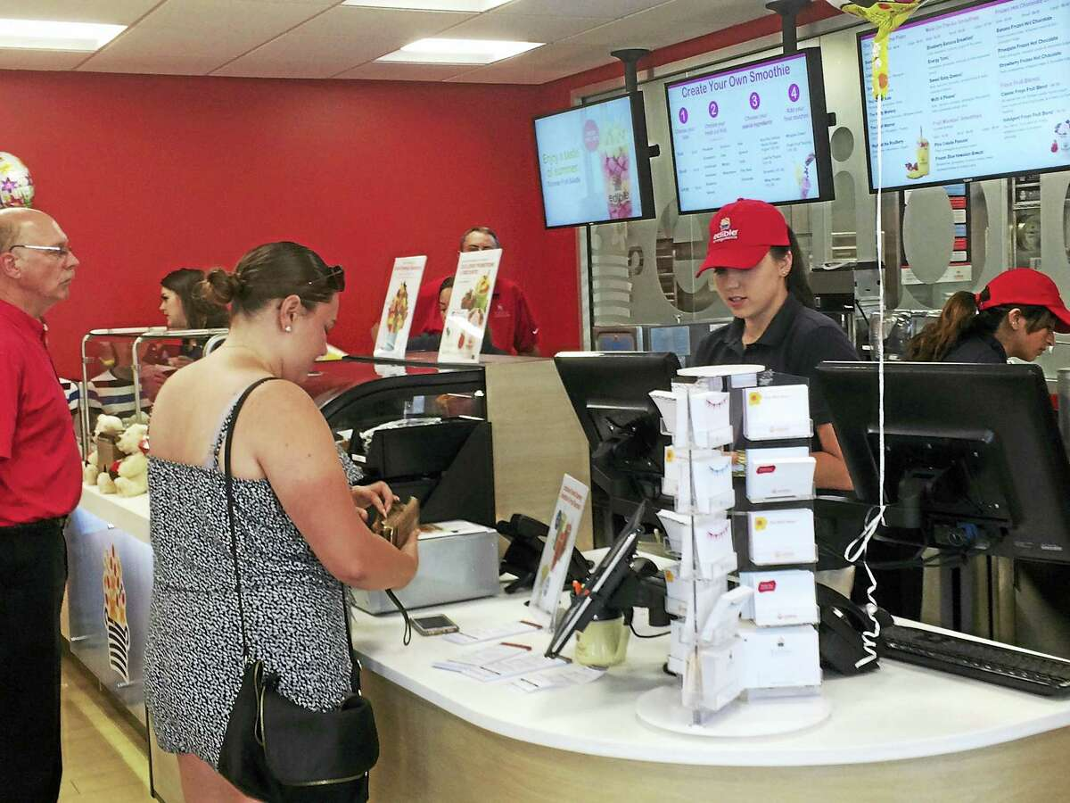 A customer pays for her fresh fruit smoothie Wednesday at the new Edible To Go store in Wallingford, in the Edible Arrangements headquarters.