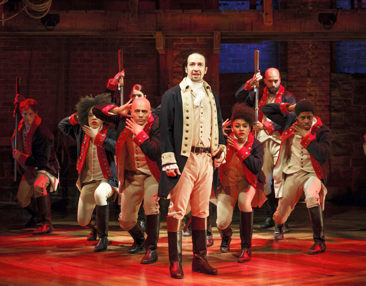 """This image released by The Public Theater shows Lin-Manuel Miranda, foreground, with the cast during a performance of """"Hamilton,"""" in New York. A PBS special this fall on the Tony Award-winning musical will feature at least 15 minutes of performance footage with creator Lin-Manuel Miranda and his team."""