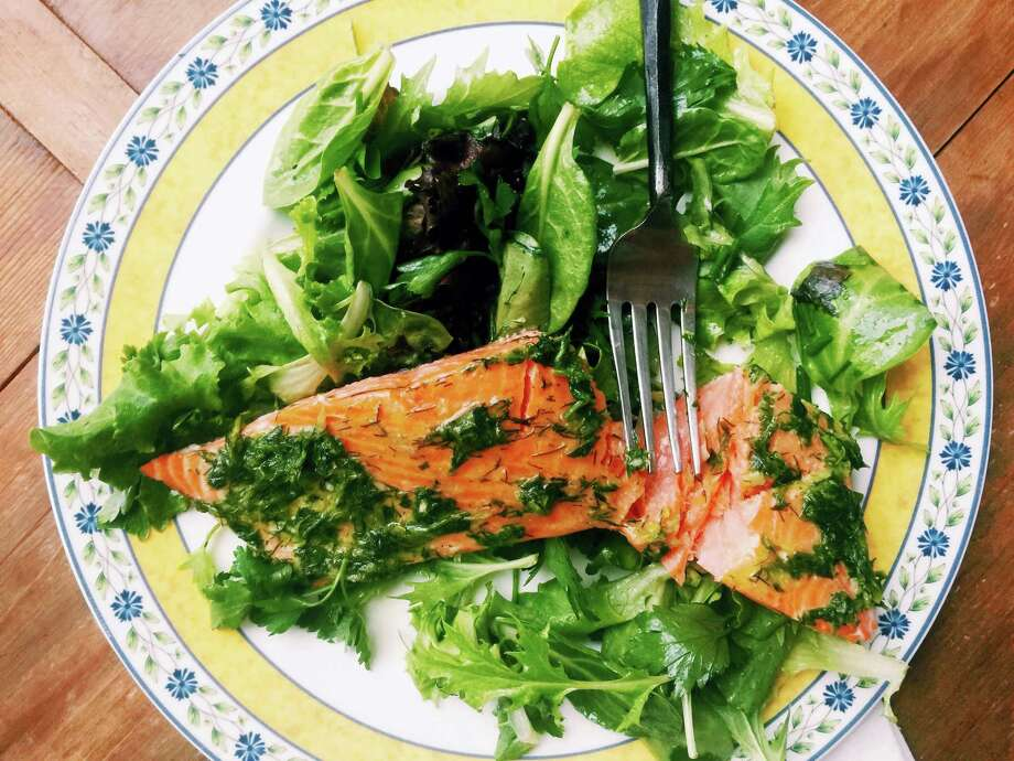 This warm-weather recipe combines salmon bathed in olive oil and herbs with spring-y greens and salad. It's the kind of lighter, brighter meal we tend to want during summer. Photo: Katie Workman — The Associated Press  / Katie Workman