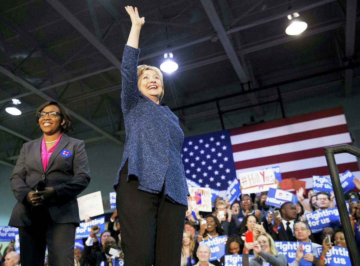 Democratic presidential candidate, Hillary Clinton, right, waves to the crowd as she takes the stage for a campaign event at Miles College as Jynae Jones, president of the student government association looks on Saturday, Feb. 27, 2016, in Fairfield, Ala.