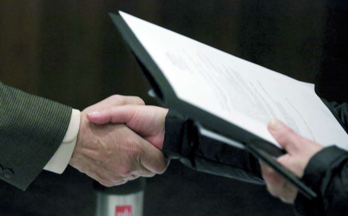 In this April 22, 2015, file photo, Ralph Logan, general manager of Microtrain, left, shakes hands with a job seeker during a National Career Fairs job fair in Chicago. On Thursday, March 3, 2016, the U.S. Labor Department reports on the number of people who applied for unemployment benefits a week earlier.