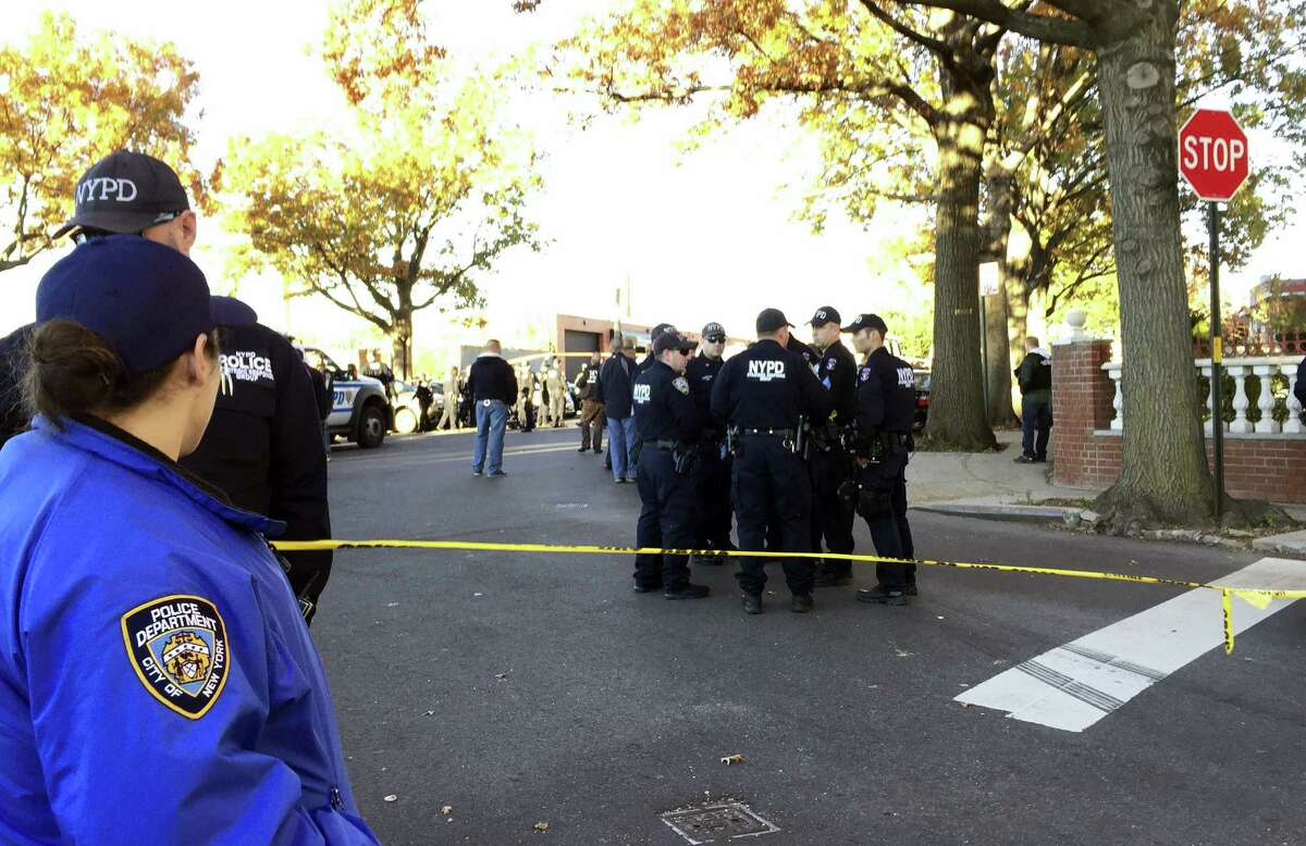 New York City Police Officers gather at a shooting scene in the Bronx borough or New York, Friday, Nov. 4, 2016. Authorities say two New York City police sergeants have been shot in a gun battle with a robbery suspect. A police spokesman says the robbery suspect was killed in the gun fire exchange.