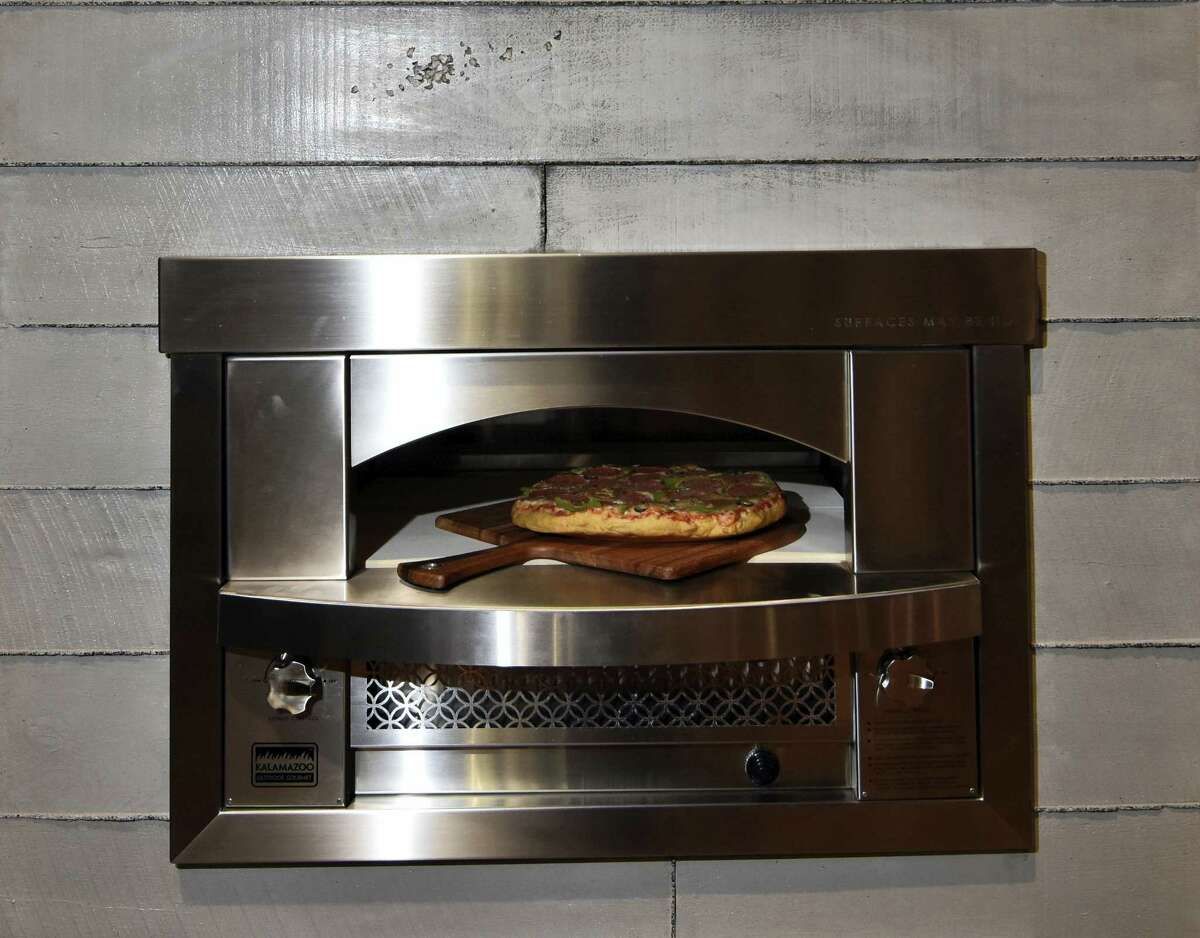 This Jan. 2016 photo provided by Kalamazoo Outdoor Gourmet shows the $8,300 built-in Artisan Fire Pizza Oven that was on display at the Kitchen and Bath Industry Show, in Las Vegas. Pizza ovens for the kitchen or the backyard were one of the hot trends at this year's Kitchen and Bath Industry Show in Las Vegas.