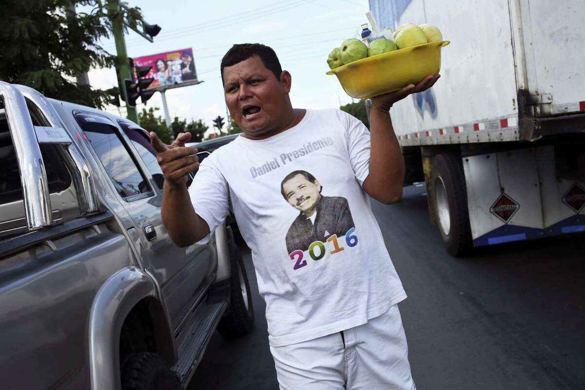 A street vendor wearing a T-shirt with political propaganda in favor of President Daniel Ortega sells guavas and oranges on the Panamerican highway in Managua, Nicaragua, Thursday.