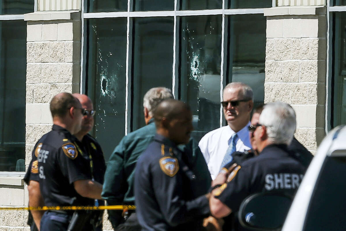 Law enforcement stand in front of windows pierced by bullet holes at Knight Transportation after an employee, who was terminated last month, returned to the business and fatally shot a co-worker before killing himself, Wednesday, May 4, 2016 in Katy, Texas.
