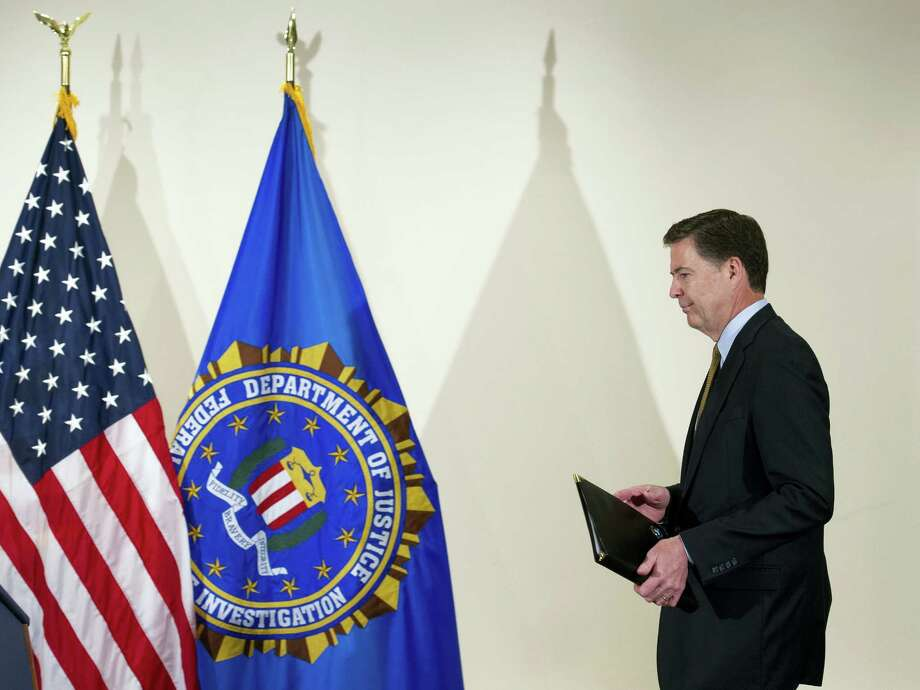 FBI Director James Comey walks to the podium to make a statement at FBI Headquarters in Washington Tuesday. Photo: Cliff Owen — THE ASSOCIATED PRESS  / Cliff Owen