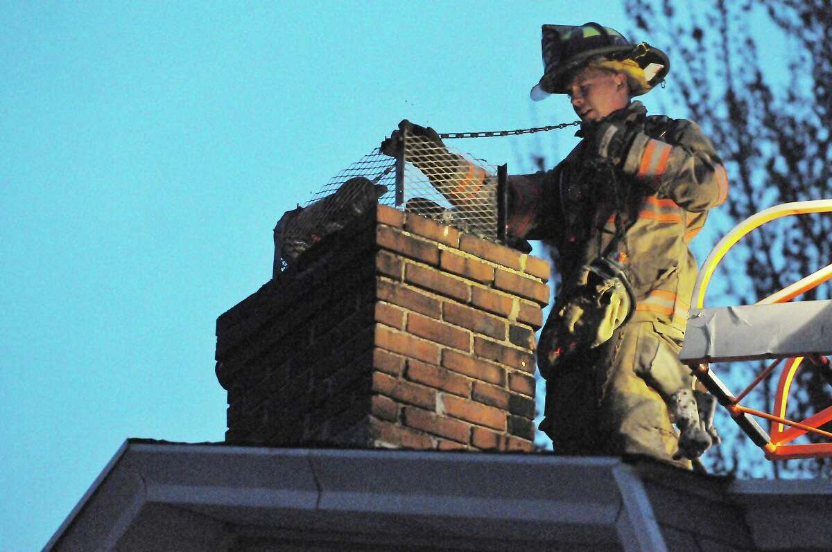 A South Fire District firefighter uses a chain to loosen debris after a chimney fire in Middletown.