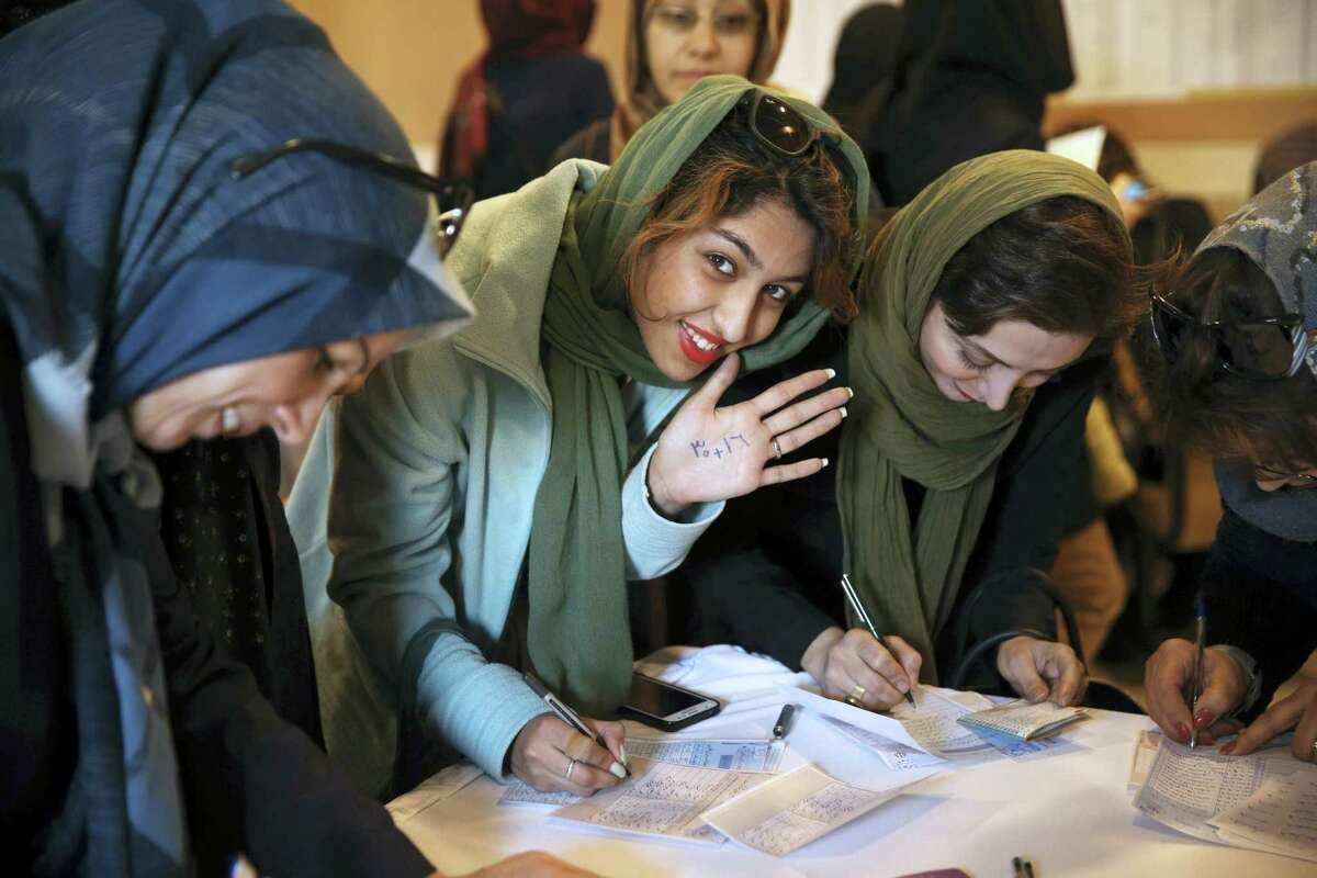 In this Feb. 26 photo, an Iranian voter shows her hand with numbers 30+16, a reformists slogan urging people to vote all reformists and moderate candidates in Tehran, for both parliament and Assembly of Experts elections, as she fills out her ballot in a polling station in Tehran, Iran.