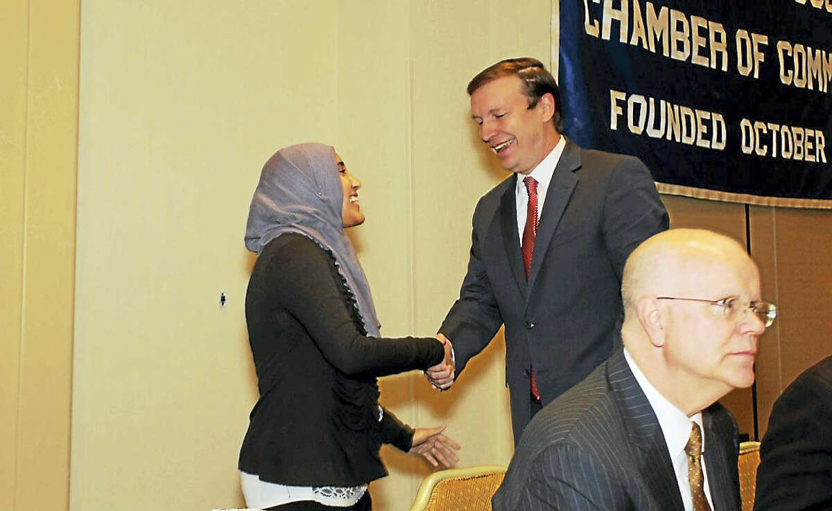 From left, Madiha Shafqat shakes U.S. Sen. Chris Murphy's hand as State Comptroller Kevin Lembo sits in the foreground at this week's Middlesex County Chamber of Commerce member breakfast in Cromwell.