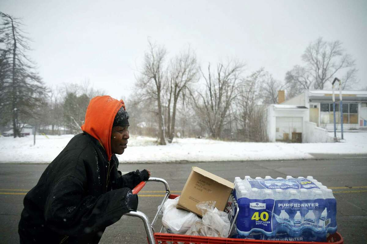 Ulunda Green walks with a cart full of food and water to her home after the first Food Bank food distribution on Wednesday, Feb. 24, 2016, in Flint, Mich. The Food Bank of Eastern Michigan of Flint is partnering with the Michigan Department of Health and Human Services to provide truckloads of food in February and March. Officials say the mobile food pantry will be used in Flint to help increase access to nutritious food that can limit the effects of lead exposure.