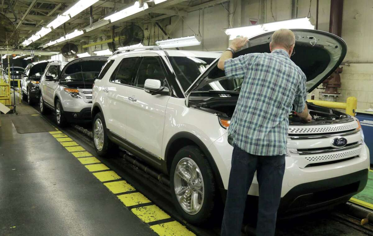 In this Oct. 22, 2014 photo, workers perform final inspections on 2015 Ford Explorers on the assembly line at the Chicago Ford Assembly Plant in Chicago.