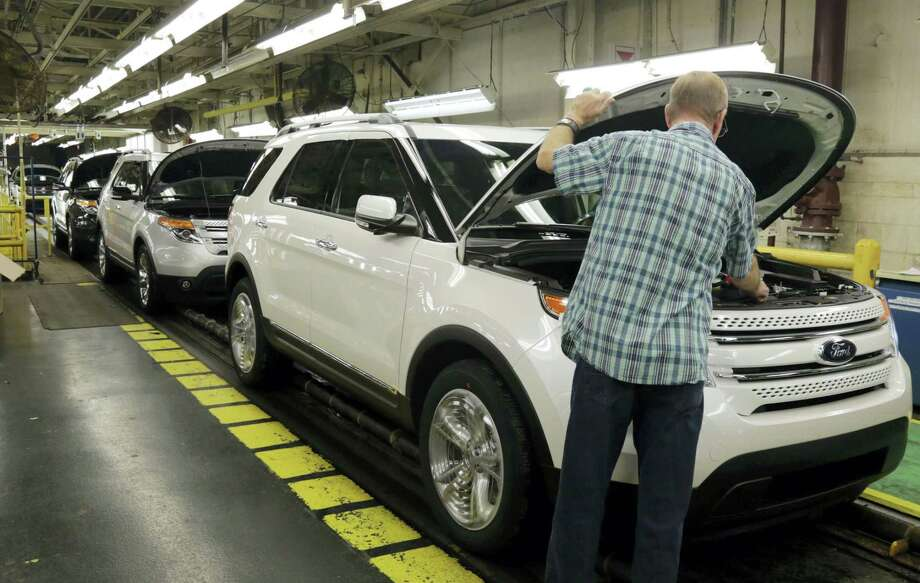 In this Oct. 22, 2014 photo, workers perform final inspections on 2015 Ford Explorers on the assembly line at the Chicago Ford Assembly Plant in Chicago. Photo: AP Photo/M. Spencer Green  / AP