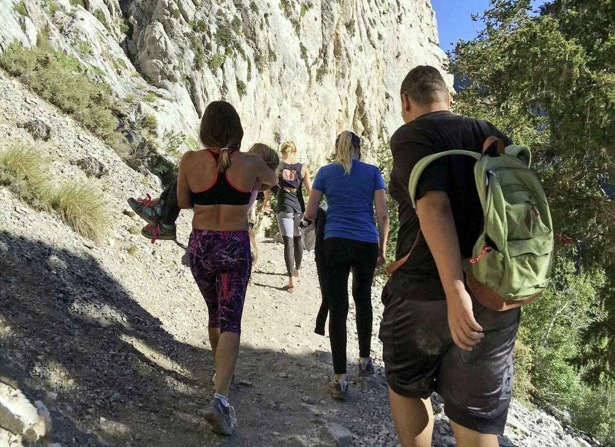 In this Sept. 4, 2016 photo provided by Myra Fukuno, former mixed martial arts Ultimate Fighting Championship women's bantamweight champion Miesha Tate, left, carries a little girl with a broken arm down Mount Charleston near Las Vegas. Tate says she's inspired by the tough little girl who broke her arm while hiking near Las Vegas.