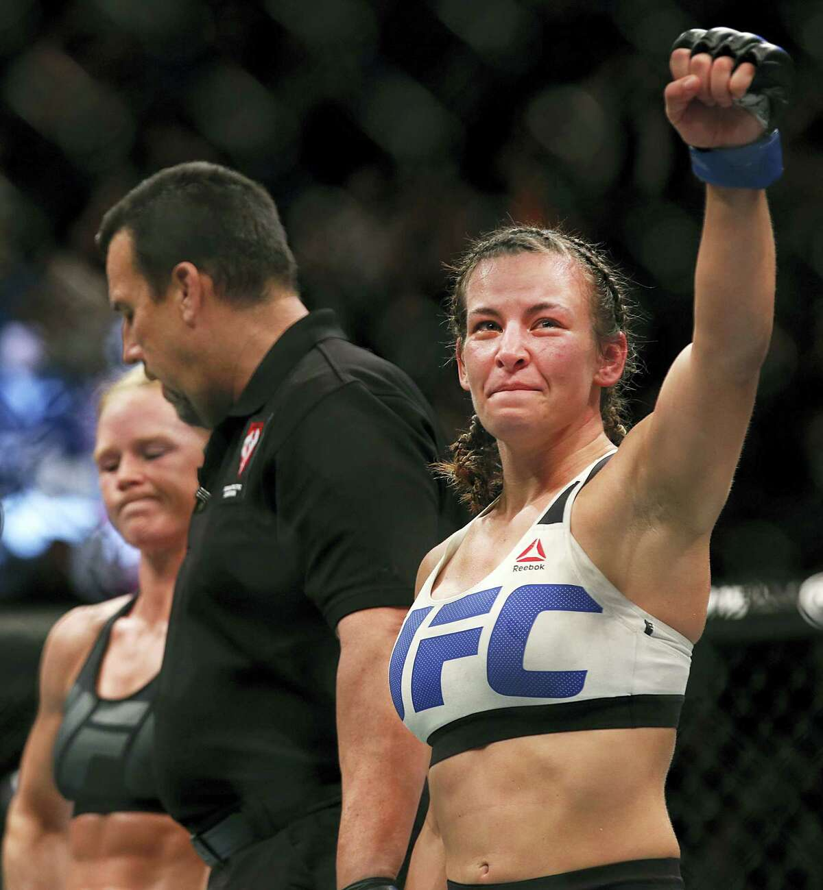 In this March 5, 2016 photo, Miesha Tate, right, celebrates her victory over Holly Holm in a UFC 196 women's bantamweight mixed martial arts bout in Las Vegas.