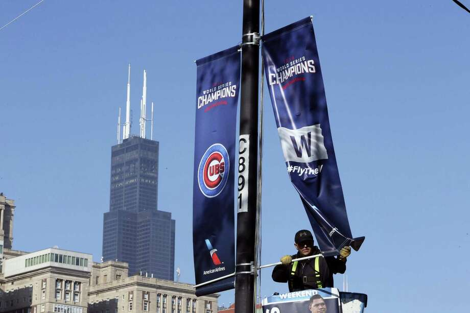 Chicago Cubs banners are installed in preparation for the parade and rally to celebrate the Cubs World series victory. Photo: Antonio Perez — Chicago Tribune Via AP  / Chicago Tribune