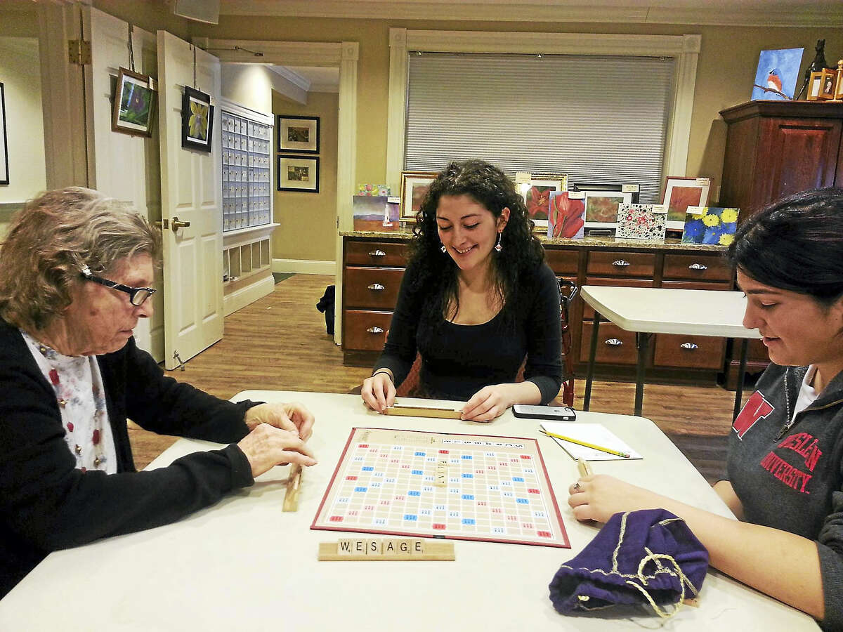 Wesleyan students Sheri Reichelso, center, and Jenna Starr, right, play a game of Scrabble with a nursing home residents.