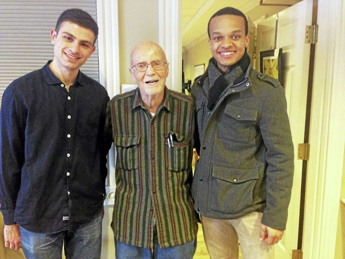 From left are Wesleyan students Derrick Fossi, left, and Matthew Lynch, right, sharing a moment with nursing home resident left Doc. Participants say the WesAGE program motivates students and encourages Middletown assisted-living residents to remain active.