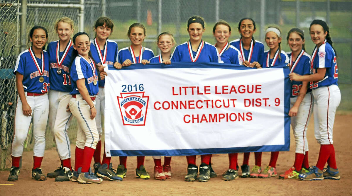 Jimmy Zanor - The Middletown PressThe Coginchaug Little League Softball team celebrates with the District Championship banner Sunday night at George Atwell Field.