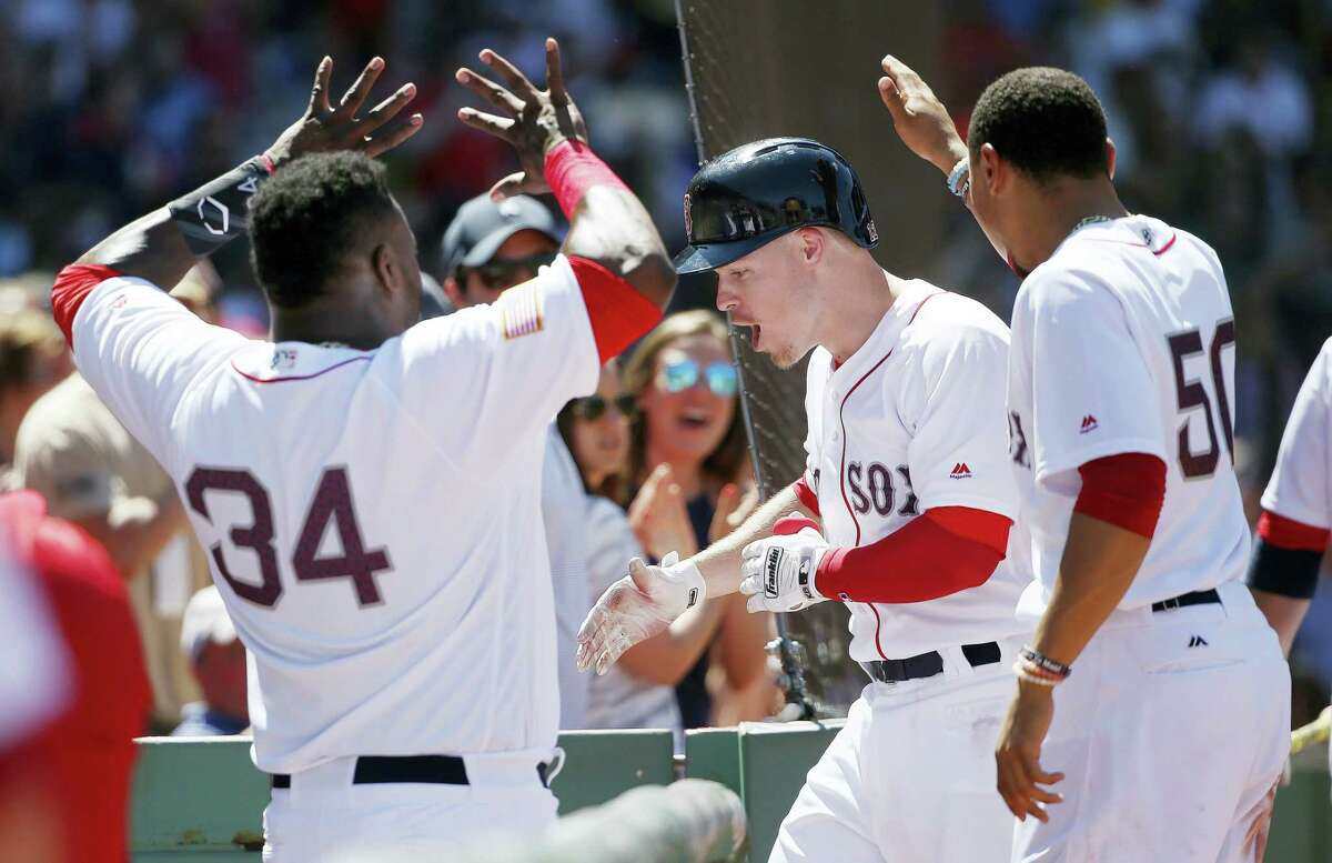 Boston's Brock Holt, center, celebrates his two-run home run during the third inning against the Texas Rangers in Boston. The Red Sox won 12-5.
