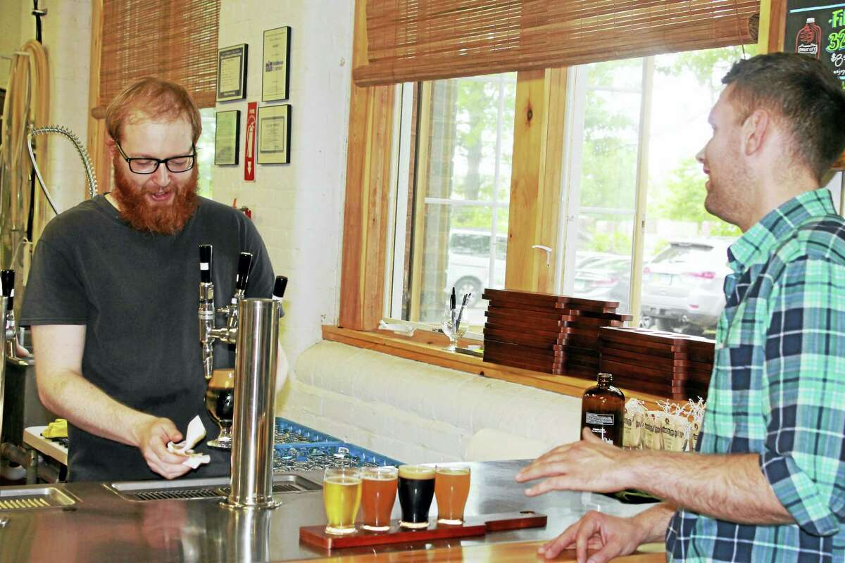A brewer at work: Owner and Brewer Chris Coughlin serves up a draft beer of Nitro Stout to a customer at his bar located in his brewery's headquarters.