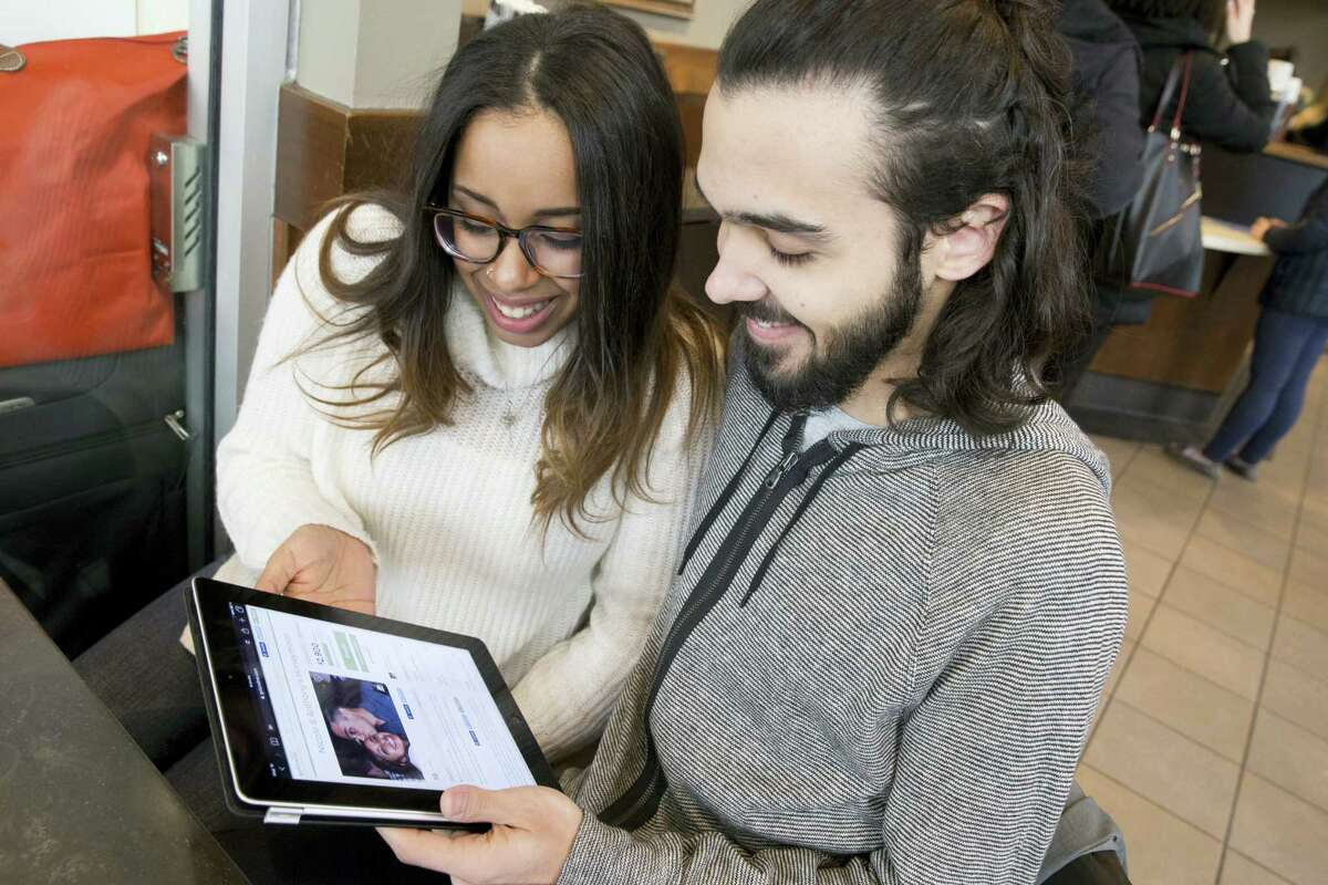 Nicole DePinto, left, and her husband, Anthony, pose for a photo Tuesday with their crowdfunding page displayed on an iPad, in New York. Websites such as Honeyfund, GoFundMe and Honeymoon Wishes make it easy to raise cash for a post-wedding getaway.
