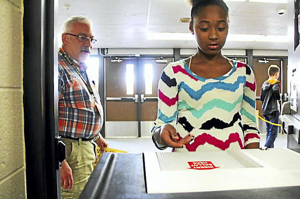 Kathleen Schassler — The Middletown Press Seventh-grader Gabrielle Gadlin feeds an official 2016 Middletown ballot into a voting machine as paraprofessional Mr. Civetelo looks on. The long tradition of straw polling at Woodrow Wilson Middle School started in 1963.