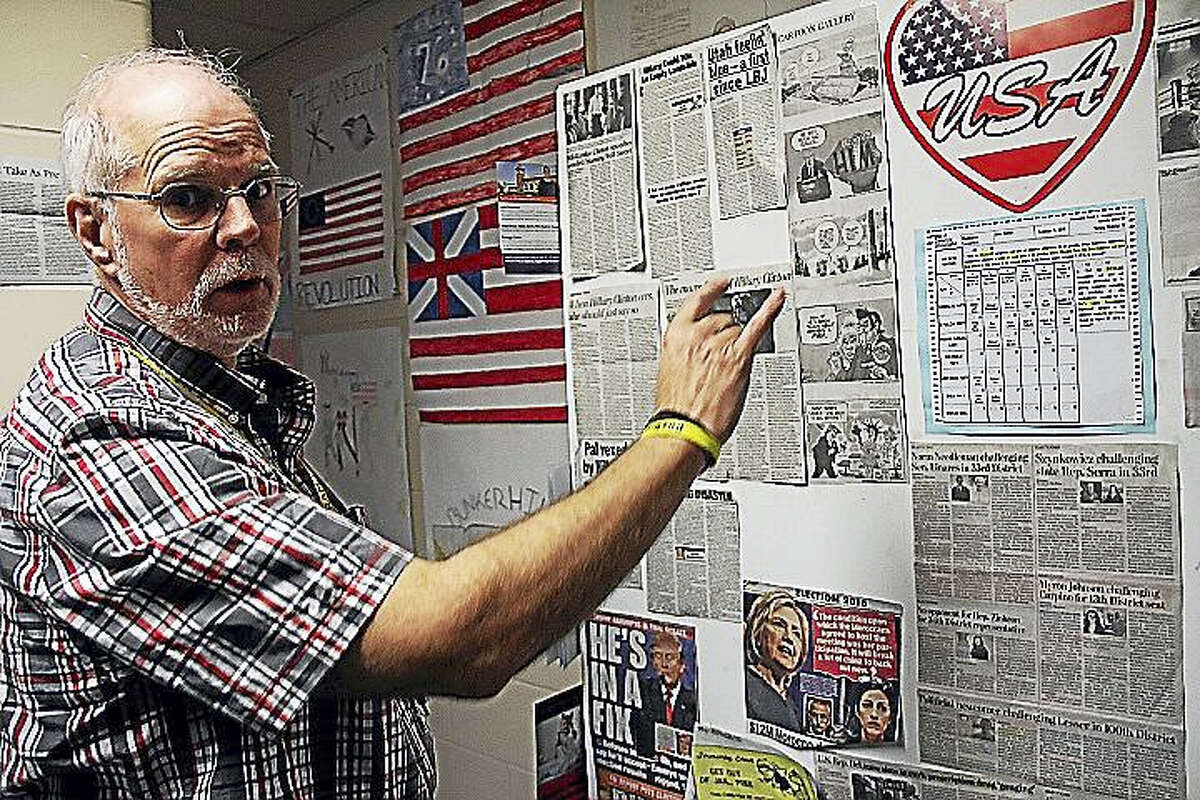 Woodrow Wilson Middle School history teacher John Geary points to a collection of election news collected by seventh-graders this month.