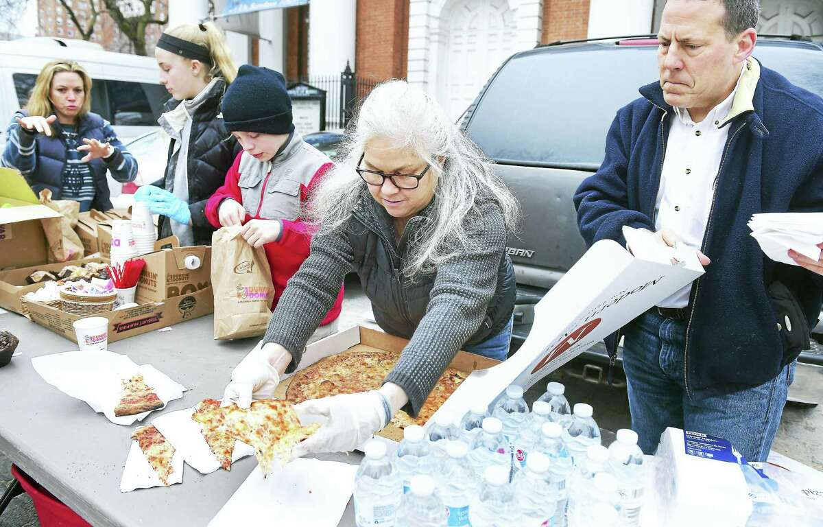 Jennifer Page, center, of Guilford and Jack Walker, right, of Clinton put out slices of Modern Pizza for the homeless in front of the Center Church on the Green in New Haven Tuesday. Coffee and muffins, along with coats, blankets and other clothes, were distributed. Every third Tuesday, Shoreline volunteers come to distribute food and clothes to the homeless at this location. Modern Pizza donates 40 pizzas a month for the cause.