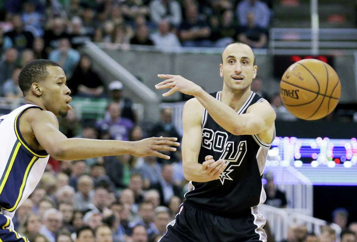 In this April 5, 2016 photo, Utah Jazz guard Rodney Hood, left, guards San Antonio Spurs guard Manu Ginobili (20) as he passes the ball during the second quarter of an NBA basketball game in Salt Lake City. Ginobili said he is coming back for a 15th season in the NBA. Ginobili made the announcement on his personal blog Sunday, July 3, 2016.