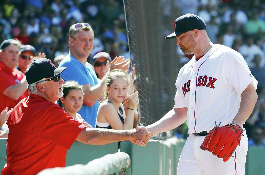 Red Sox starting pitcher Sean O'Sullivan is congratulated by pitching coach Carl Willis after leaving the game during the sixth inning Sunday. Photo: Winslow Townson — The Associated Press  / FR170221 AP