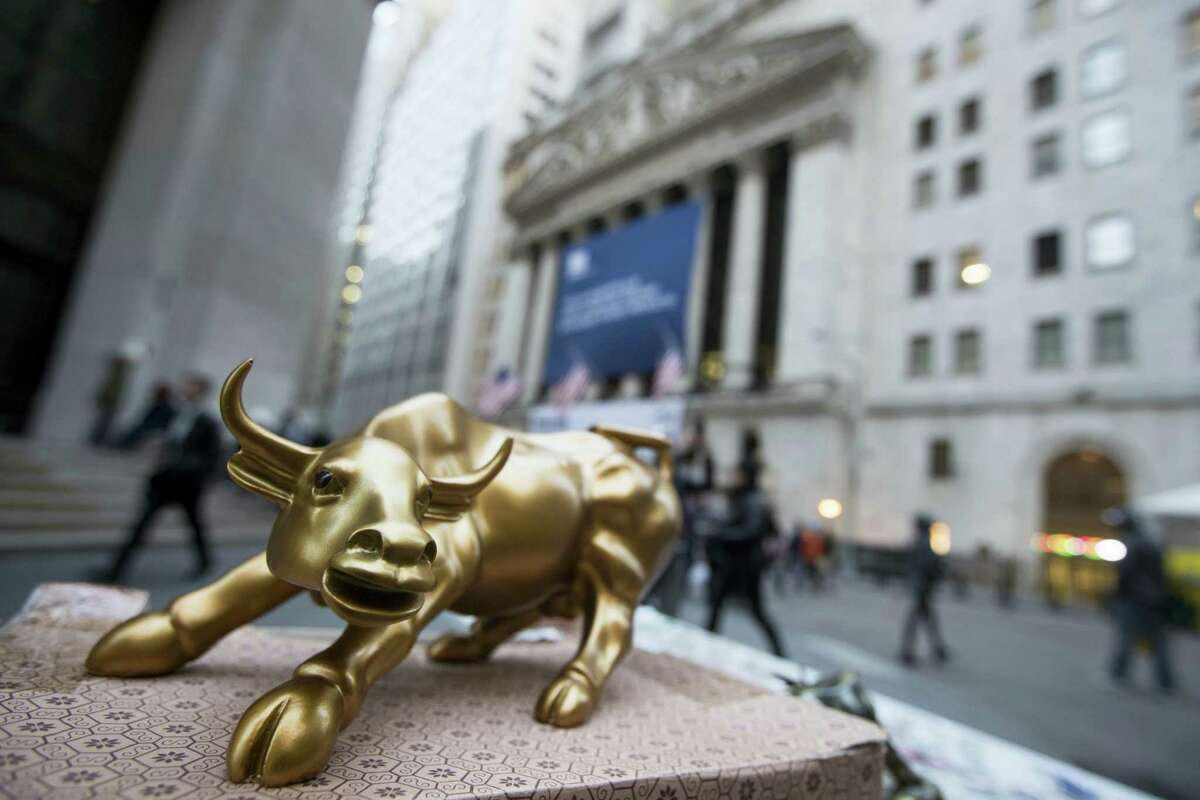 """In this Tuesday photo, a miniature reproduction of Arturo Di Modica's """"Charging Bull"""" sculpture sits on display at a street vendor's table outside the New York Stock Exchange, in lower Manhattan."""