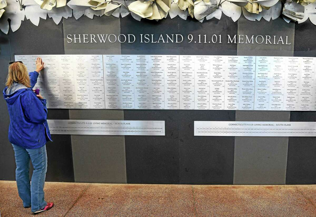 Sue Monroe of Stratford places her hand over the plaque honoring Thomas Brennan at the Sherwood Island 9/11 Memorial at Sherwood Island in Westport in this photo from last year.