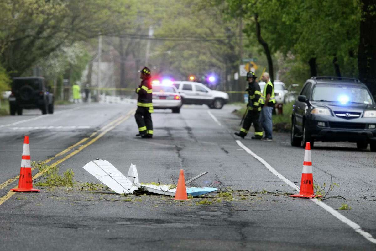 Traffic cones mark the position of pieces from a Beech BE-35 light plane after the aircraft crashed in a residential neighborhood in Syosset, N.Y., Tuesday, May 3, 2016. A spokesman for the Federal Aviation Administration said the plane that had taken off from Myrtle Beach, S.C. and was headed to Robertson Field, an airport in Plainville. All three aboard the plane died in the crash.
