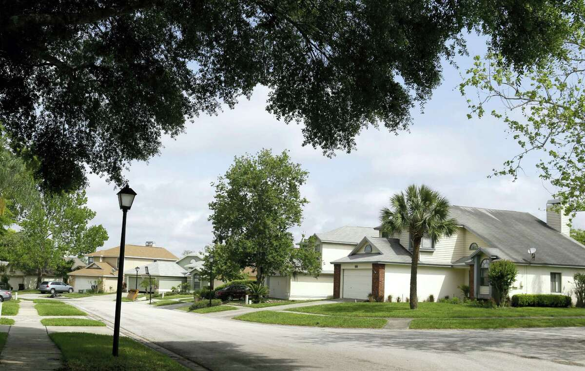 This April 14, 2016 photo shows a view of a street in the Piedmont Park neighborhood in Apopka, Fla. Many of the single-family homes in the neighborhood used to be owned by families, but now they're owned by companies associated with big real estate investment firms. And the occupants are tenants, not owners.