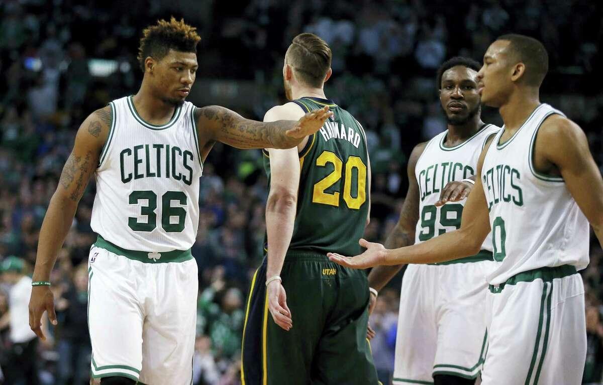 Boston Celtics' Marcus Smart (36), Jae Crowder (99) and Avery Bradley (0) celebrate defensive play as Utah Jazz's Gordon Hayward (20) walks away during the fourth quarter of an NBA basketball game in Boston, Monday, Feb. 29, 2016. The Celtics won 100-95. (AP Photo/Michael Dwyer)