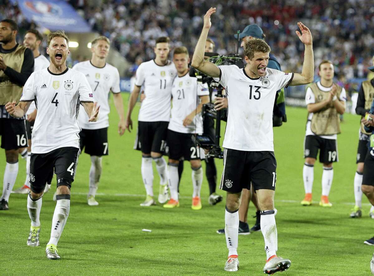Germany's Thomas Mueller, right, celebrates with teammates after Germany won the penalty shootout against Italy on Saturday.