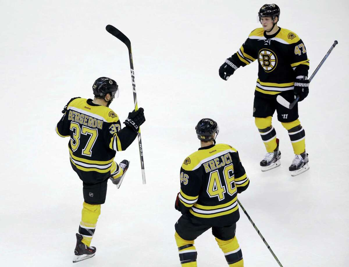 Bruins center Patrice Bergeron (37) celebrates his go-ahead goal with teammates David Krejci (46) and Torey Krug (47) in the third period Tuesday.