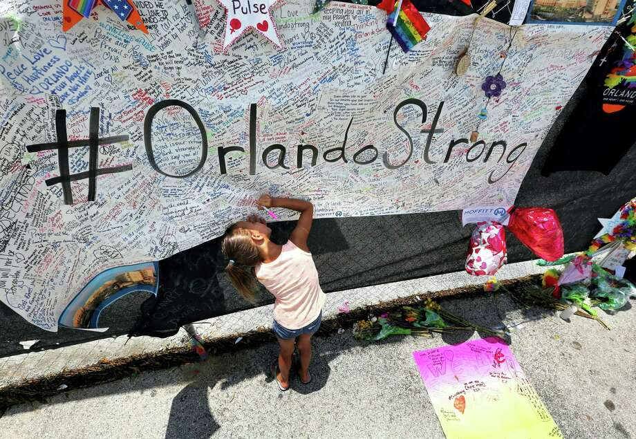 Seven-year-old Kyndall Whitley signed a poster Wednesday as visitors continued to flock to the roadside memorial at the Pulse nightclub in Orlando, Florida. Photo: Joe Burbank — Orlando Sentinel Via AP  / Orlando Sentinel