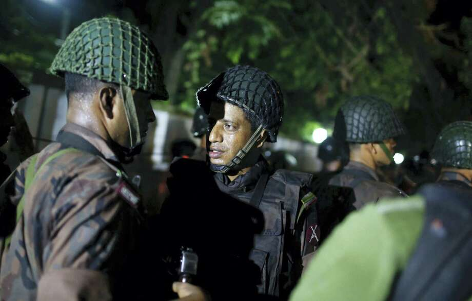 Bangladeshi security personnel stand guard near a restaurant that has reportedly been attacked by unidentified gunmen in Dhaka, Bangladesh, Friday, July 1, 2016. Local media reported that a group of attackers took hostages inside a restaurant frequented by both locals and foreigners in a diplomatic zone in Bangladesh's capital. Photo: THE ASSOCIATED PRESS / Copyright 2016 The Associated Press. All rights reserved. This material may not be published, broadcast, rewritten or redistribu