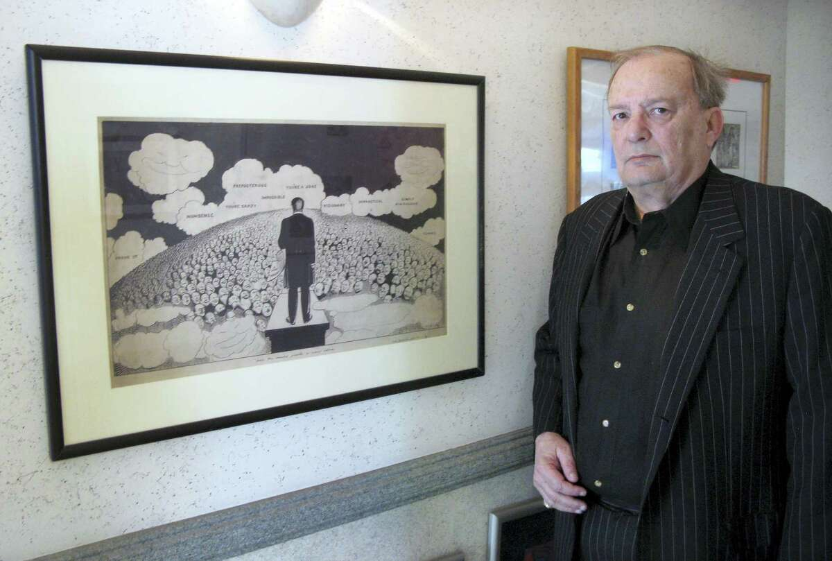 In this April 29, 2016 photo, attorney Bruce Rubenstein, a collector of left-wing political memorabilia, stands in front of a 1920s drawing by political cartoonist Art Young on April 29, 2016 inside his office in Hartford, Conn. Rubenstein is threatening to sue the University of Hartford which plans to sell a political memorabilia collection to which Rubenstein donated hundreds of items.