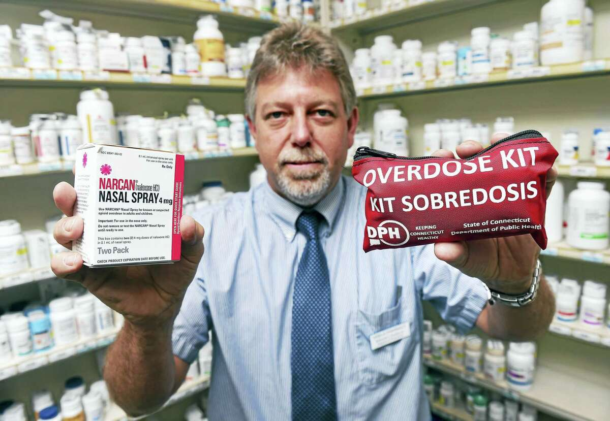 Edmund Funaro Jr., director of Visels Pharmacy, holds Narcan nasal spray, left, and a Connecticut Department of Public Health overdose kit at the pharmacy in New Haven.