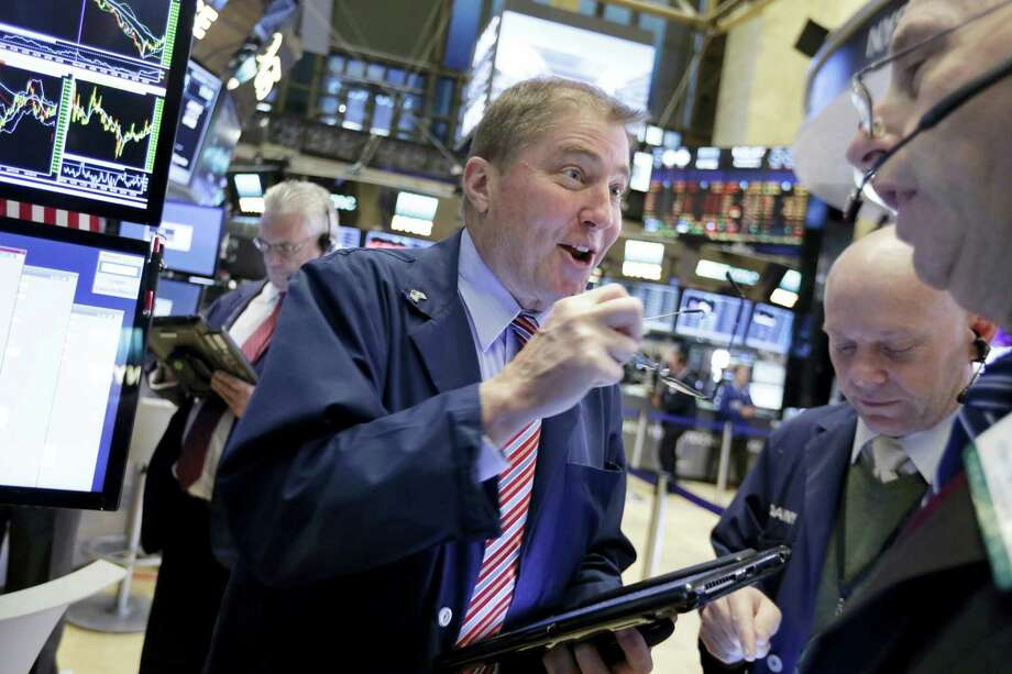 Trader David Williams, center, works on the floor of the New York Stock Exchange Wednesday. Photo: Richard Drew — The Associated Press  / AP