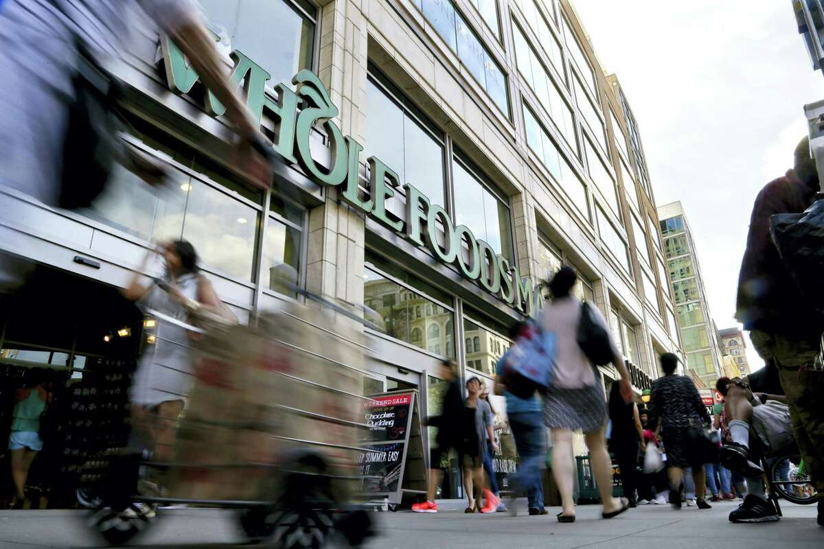 Pedestrians pass in front of a Whole Foods Market store in Union Square in New York.