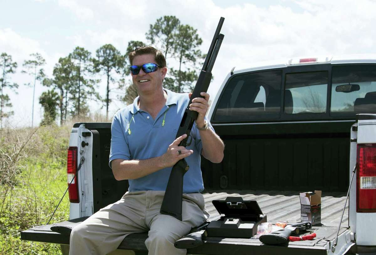 """In this photo taken April 7, 2016, Jonathan Mossberg, whose iGun Technology Corp. is working to develop a """"smart gun,"""" poses with the firearm, in Daytona Beach, Fla. Mossberg is among a group of pioneers looking to build a safer gun."""